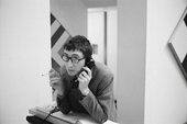 Photograph of John Kasmin at the desk in his gallery during an exhibition of paintings by Kenneth Noland in 1967
