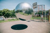 photograph of of the artist Allard and a large silver ball mid bounce in a basketball court
