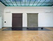 Photograph of a large installation by Joseph Beuys in the Staatsgalerie Stuttgart, Germany. Two tarpaulin-like objects – one made of rubber, the other felt – are installed on the wall and touch down to the floor in a thick, heavy bulge.