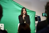 woman holding a microphone in front of a green screen