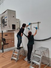 Two people hold a bracket up against a gallery wall, one is up a step ladder