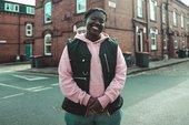 Portrait of Melz Owusu wearing a pink hoodie and black vest, standing in a schoolyard