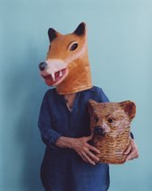 Joan Jonas wearing a fox mask and holding a bear mask