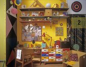 Chapters One to Five, 2012, Production Stillof colourful studio with shelves, desk, chair and hanging mobiles