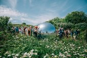 photograph of a large Silver Ball in amongst wildflowers with people stood around