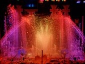 film still from the watershow extravaganza. shoots of water brightly lit with pink and red lighting