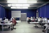Photograph of a large room with blue walls and concrete floors, lit by bright fluorescent strip-lights on the ceiling. There are a number of white office desks with a desktop computer on each. Some people sit on red swivel chairs at the computers.