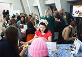 people sit at a table in Tate Modern and embroider on a square of yellow fabric
