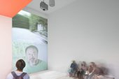 Man looks onto a wall where Ai Weiwei's face is being projected