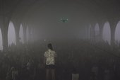A woman stands in front of a crowd of people in a large hall