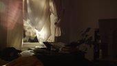 Film still of window curtain of bedroom, light shines through