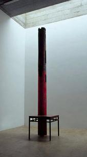 A metal pillar stands inside a metal table