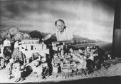 A black and white photograph of Ray Harryhausen standing with an Olympus minature