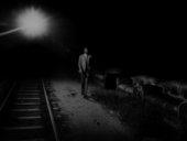 photograph of a man walking along a railway track at night