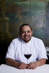 Photograph of Tate Britain Head Chef Alfio Laudani holding a glass of wine