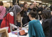 A group of young people lean across a stand, talking and looking at printed material, at the Alternative Careers Fair