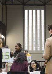 Young people smiling as they engage with visitors at the Alternative Careers Fair with the distinctive vertical windows of the Tate Modern Turbine Hall behind