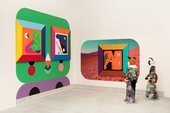 two standing sculptures with fox heads stand in a gallery space looking at two brightly coloured, geometric paintings