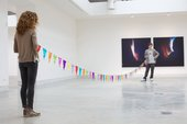 Two people stand at either end of a gallery space, holding up a string of multi-coloured bunting