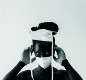 Black and white photo of the artist wearing bandages on their face