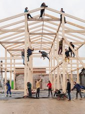 The artist collective Assemble sit and stand by a shed