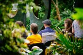 People sat in the Barbara Hepworth Museum and Sculpture Garden in St Ives listening to music