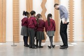 A group of children looking at an artwork with a teacher