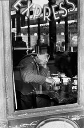 A black and white photograph of Alberto Giacometti sitting in a Parisian cafe