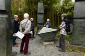 A tour guide talks to a group of people in front of the artwork Conversation with Magic Stones by Barbara Hepworth at the Barbara Hepworth Museum