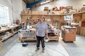Phyllida Barlow stands in her art studio, with wooden workbenches behind her and wooden shelving on the back wall.