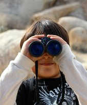 photograph of a child looking through binoculars