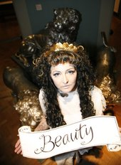 Photograph of a long haired person wearing a crown holding a banner which reads 'Beauty'