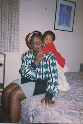 A mother sitting on a bed holding her child