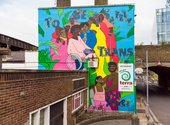 A bright mural reading to be safely trans outside, surrounded by Black trans and gender non-confirming folks