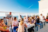 Groups of people sit at the tables enjoying food and drinks at Tate St Ives' cafe