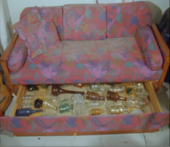 Film still showing bottles under a sofa