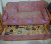 Film still showing bottles under a sofa