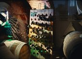 Film still of wine bottles in a cellar