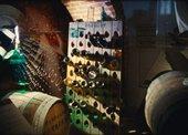 Film still of wine bottles in a cellar