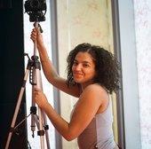 Ranya adjusts a camera tripod and smiles
