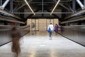 gallery visitors walk through a set of doors and a corridor with markings on the floor