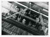 A group of Bauhaus weavers looking through the loom in to the camera