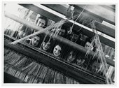 a group of female weavers looking at the camera through the loom
