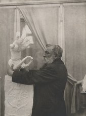 Rodin placing the plasterClenched Hand with ImploringFigure on a pedestal, in thePavillon de l'Alma, Meudon1906.Photo by unknown photographer, Musée Rodin