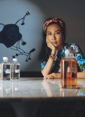 Anicka sits at a table surrounded by bottles