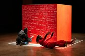 two figures on the floor in front of a large red cube
