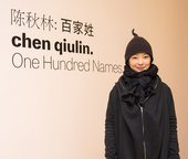 Artist Chen Qiulin stands in front of the exhibition entrance for Chen Qiulin: One Hundred Names at the Shepparton Art Museum, Australia (4 June – 24 July 2016)