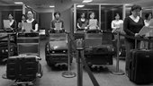 In an airport, nine Chinese spouses of Taiwanese citizens stand in front of their luggage reading a form.