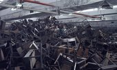 a huge pile of abandoned wooden desks and chairs, all broken on top of each other.