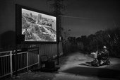 black and white high contrast image of a film being projected onto a screen in a field